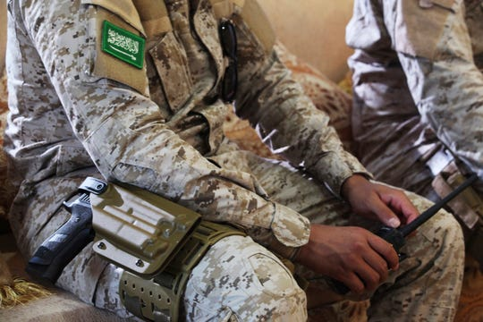 In this Nov. 28, 2018, file photo, an armed Saudi soldier holds a walkie-talkie near Mukalla, Yemen, at an airport now serving as a military base for the United Arab Emirates.
