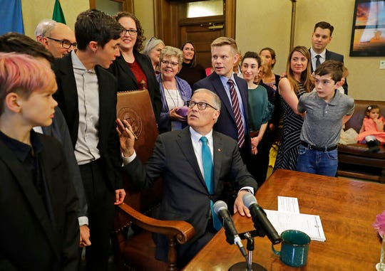 Washington Gov. Jay Inslee, center, talks with Katrina Spade, upper left, the founder and CEO of Recompose, a company that hopes to use composting as an alternative to burying or cremating human remains, Tuesday, May 21, 2019, at the Capitol in Olympia, Wash.