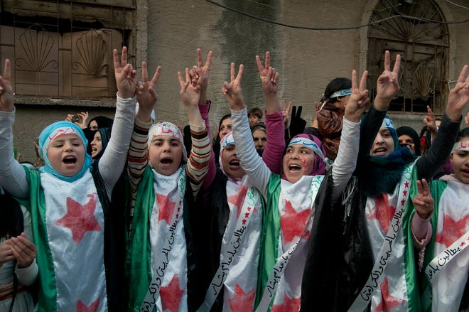 In this Dec. 21, 2011 file photo, anti-Syrian regime protesters flash the victory sign as they wear Syrian revolution flags during a demonstration in the Baba Amr area, in Homs province, Syria.