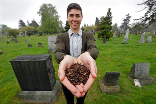 In this April 19, 2019, file photo, Katrina Spade, the founder and CEO of Recompose, a company that hopes to use composting as an alternative to burying or cremating human remains, poses for a photo in a cemetery in Seattle, as she displays a sample of compost material left from the decomposition of a cow using a combination of wood chips, alfalfa and straw.