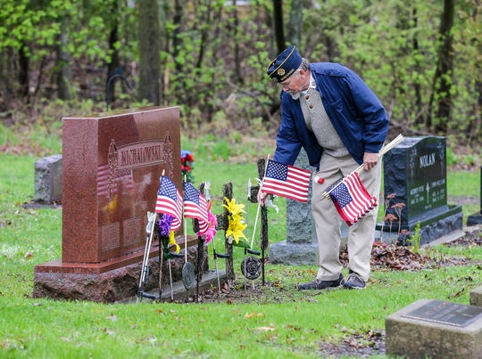 Larry Beuthin of the Brandon-Fairwater Legion Post places flags on veterans graves Thursday, May 9, 2019, in St. Mary's Cemetery northeast of Brandon in preparation for Memorial Day. Legion members will place as many as 6,000 flags on veterans' graves in the area.
