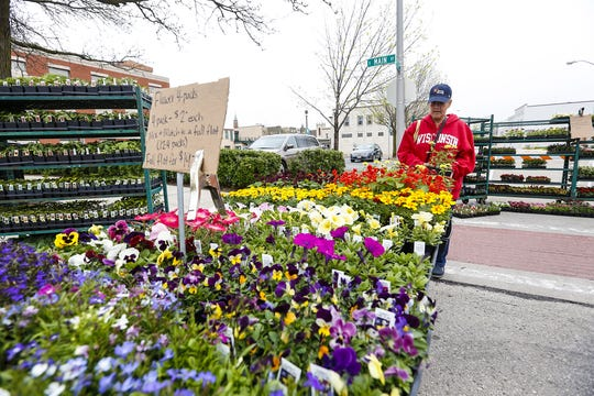 Barbara Roder, of Fond du Lac, looks at flowers Saturday, May 18, 2019 at the Farmers Market in downtown Fond du Lac, Wis.