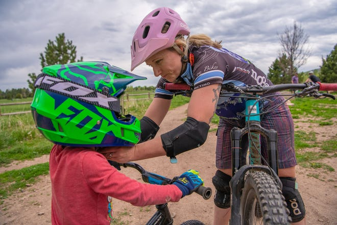 Teresa Bever helps one of her sons with his bike helmet at Spring Canyon Park in Fort Collins, Colo., on Thursday, May 16, 2019.