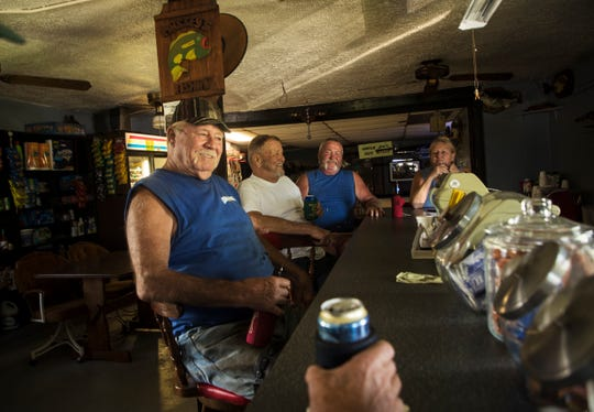 Lifelong Clewiston resident, Ronnie Olden throws back a couple of beers while talking with regulars and employees of Uncle Joe's Fish Camp along the shores of Lake Okeechobee. on Thursday, May 16, 2019. The Centers for Disease Control is doing research on the affects of blue green algae on people who work and live on or along Lake Okeechobee. Olden is taking a wait and see approach about the research. From front to back are Warren Moore, Raymond Dufek and Uncle Joe's owner Cindy Massey.