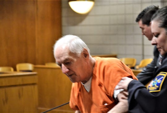 Raymand Vannieuwenhoven of Lakewood is assisted by a court security officer following a hearing Monday, May 20, in Marinette County Circuit Court. Vannieuwenhoven is charged with two counts of first degree homicide in the 1976 deaths of a Green Bay couple.