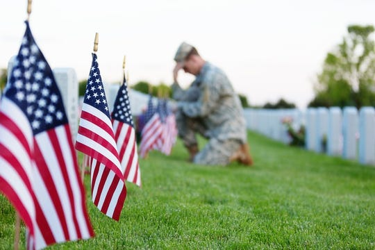 American soldier kneeling at a veteran's grave on memorial day.