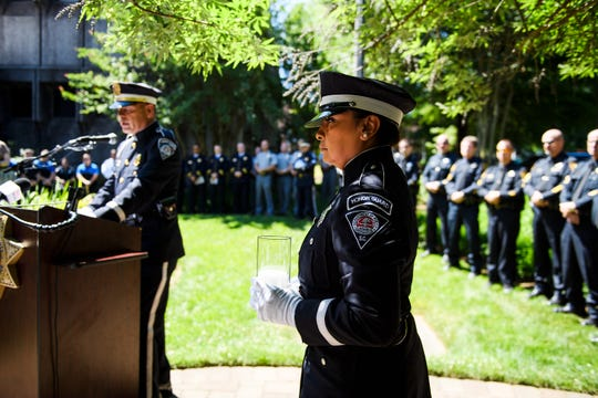 Zoila Lopez of the Greenville Police Department walks with a candle during memorial service honoring fallen Greenville County officers at the Law Enforcement Center Tuesday, May 21, 2019.