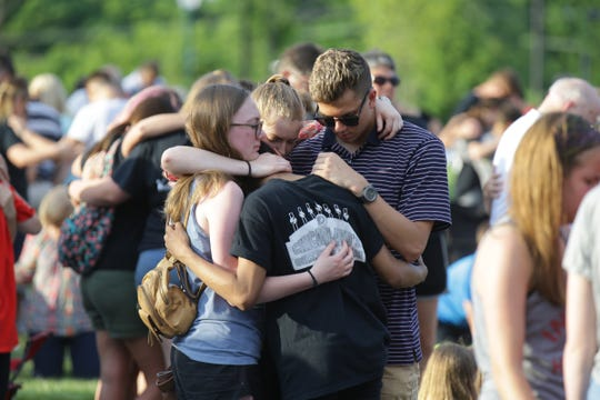 Community members pray during a vigil at Federal Hill Commons in Noblesville on May 26, 2018.