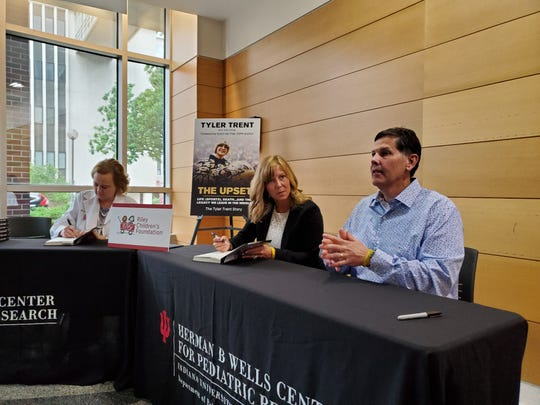 "Tony and Kelly Trent, Tyler Trent's parents, are joined by cancer researcher Dr. Karen Pollok of Wells Center for Pediatric Research and Riley Precision Genomics during a book signing for Tyler's book, ""The Upset."""