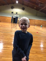 Bobby Sheffield, a 6-year old Nova Elementary student who was diagnosed with autism at 3, stands in the school's gym. After being nonverbal for three years, he began speaking a year and a half ago.