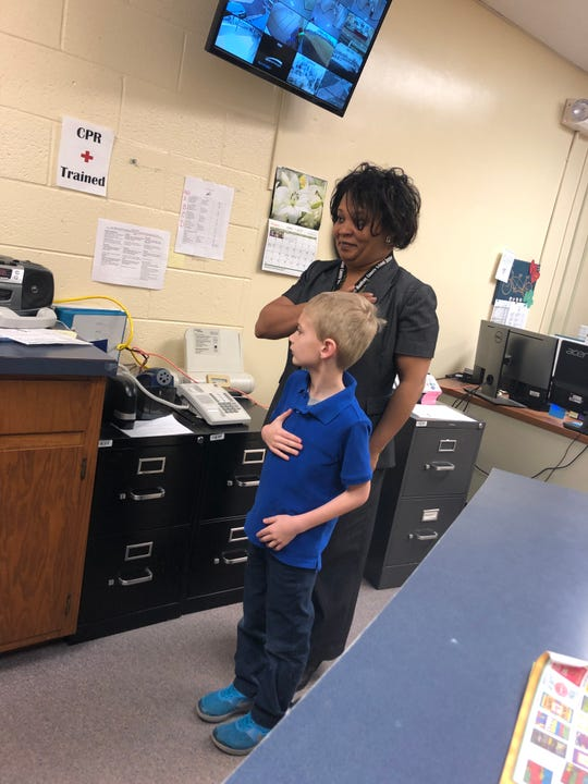 Bobby Sheffield, a 6-year student who was diagnosed with autism at 3 and was nonverbal for years, says the Pledge of Allegiance at Nova Elementary last month as the principal Tia Day stands with him.