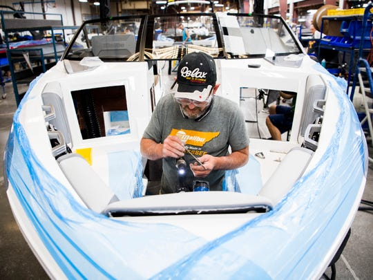 Employees install electrical components in a boat at Malibu Boat's factory in Loudon on Tuesday, May 21, 2019.