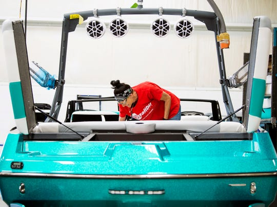 Employees work on the finishing touches on a boat at Malibu Boat's factory in Loudon on Tuesday, May 21, 2019.
