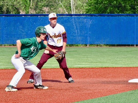 Berne Union shortstop Drew Berstler holds Fisher Catholic's Mitch Zombek on during their Division IV district semifinal at Beavers Field. The Irish won, 4-3.