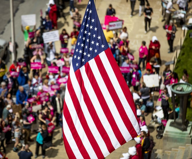 An American flag waved in the breeze at the federal building on West Broadway as protesters gathered below. May 21, 2019