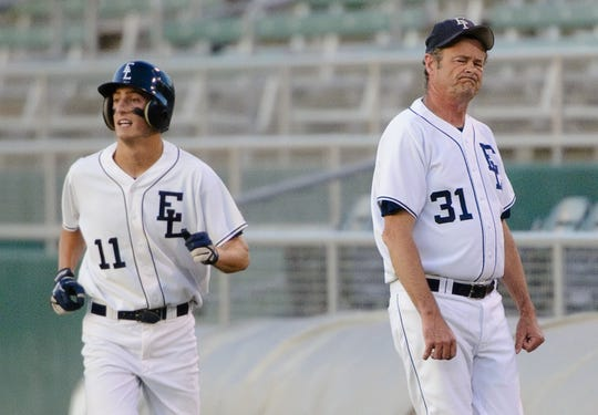 East Lansing assistant baseball coach Ed Outslay, right, is seen here in 2010 reacting to player Grant Messerschmidt being called out at first base during a Diamond Classic quarterfinal game with Fowlerville.