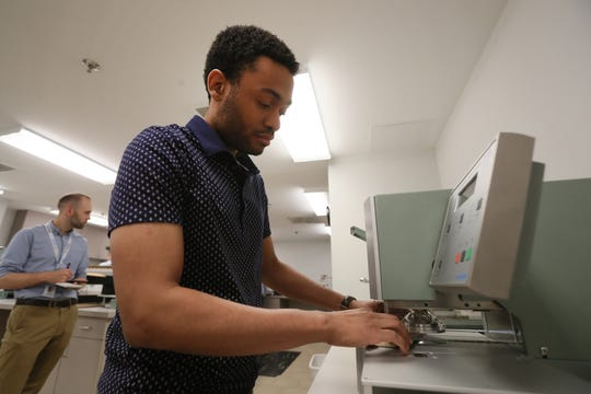 Technician Stephen Russell works in the paper testing lab at International Paper's Memphis customer commitment center on Tuesday, May 21, 2019