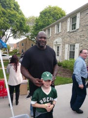 Shaquille O'Neal poses with Liam Wills on May 16 at a block party in the Enderis Park neighborhood in Milwaukee.