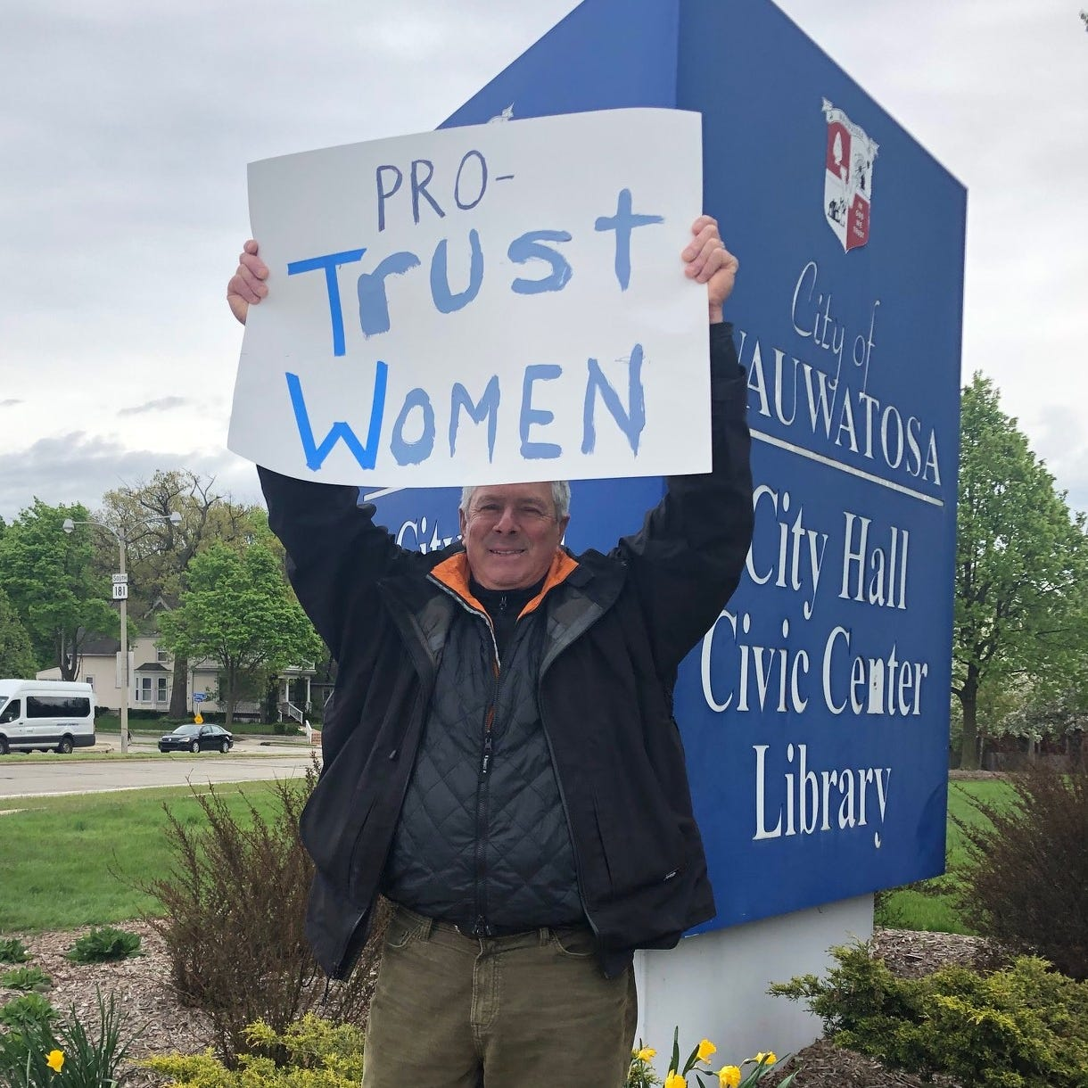 Tom Schuler of Milwaukee holds up his sign...