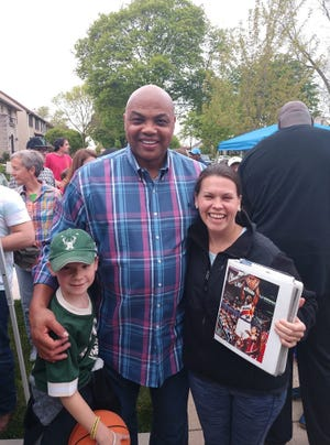 Charles Barkley poses with Liam Wills and his mom Jen Wills (holding a binder) on May 16 at a block party in the Enderis Park neighborhood in Milwaukee.