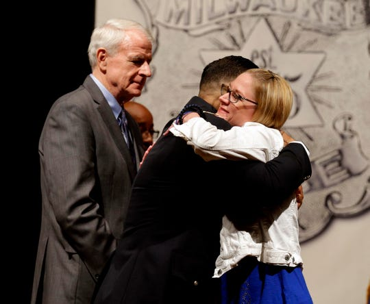 Caroline Rittner, wife of Milwaukee Police Officer Matthew Rittner, who was shot and killed while serving a search warrant, gets a hug from Police Chief Alfonzo Morales and Mayor Tom Barrett before she accepts the Medal of Honor, the highest award granted by the Milwaukee Police Department, on behalf of her late husband during the Milwaukee Police Department's Spring Merit Awards ceremony.