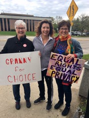Petey Lund, Jill Morin, and Cheryl Juech hold up signs during a rally on May 21 in front of Wauwatosa City Hall. On Tuesday, supporters across the nation showed opposition towards several state laws aimed at restricting access to abortions.
