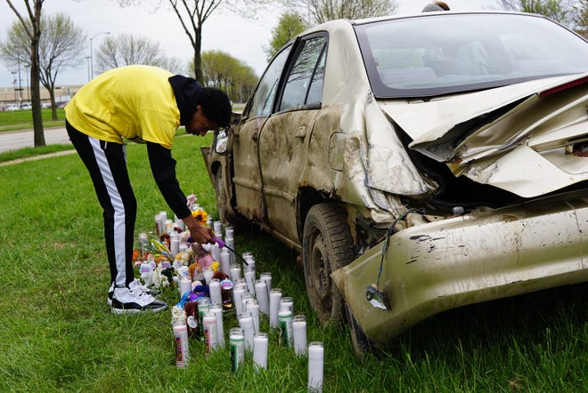 """Victor Barnett Jr., 15, lights a candle at a """"roadside memorial"""" on Tuesday afternoon created by Milwaukee teenagers at Running Rebels Community Organization, 1300 W Fond Du Lac Ave, Milwaukee. The memorial is meant to honor those who were hurt or killed in carjackings in the city. Barnett and other teens also helped to create public service videos on carjacking."""