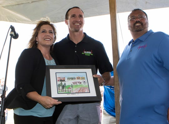 West Monroe mayor Staci Albritton Mitchell present New Orleans Saints quarterback Drew Brees with a picture during his visit to the city to promote the groundbreaking for Surge Adventure Park on May 21.