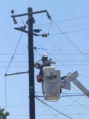 A worker installs need LED lightbulbs as a part of a citywide revamp of the municipal road lighting system