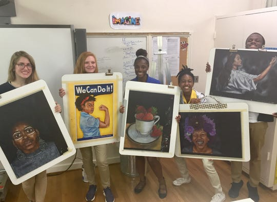 BTW art magnet senior students pose with the first piece of art each created after moving to the old Hayneville Road Elementary school.