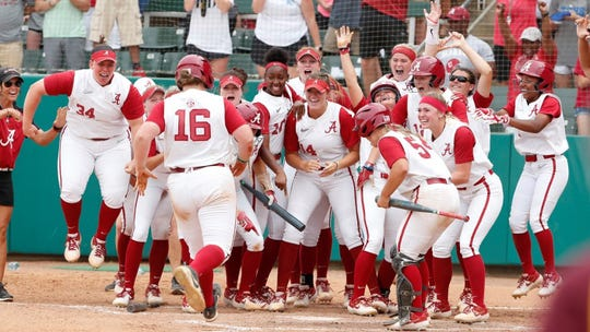 Alabama softball player Bailey Hemphill (No. 16) approaches home plate and is greeted by her teammates.