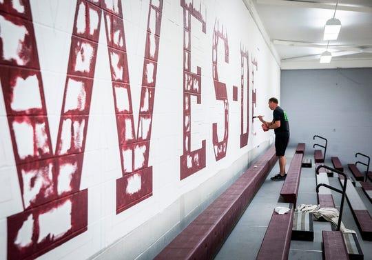 Designer Chris Mullett, owner of Mullett Design Group, paints in Wes-Del High School's gym.
