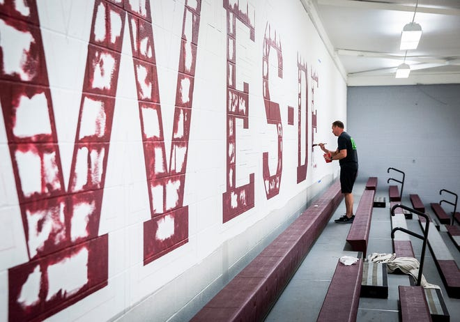 Designer Chris Mullett, owner of Mullett Design Group, paints in Wes-Del High School's gym.