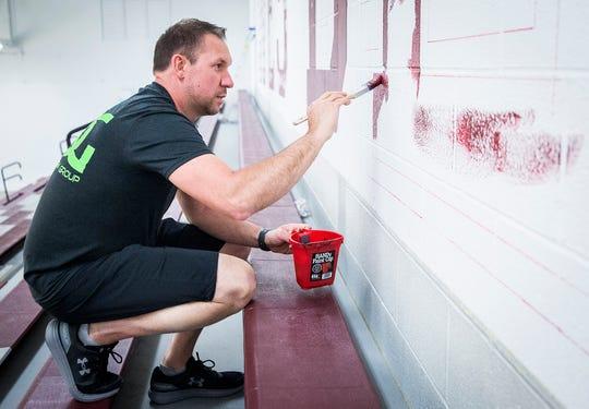 Designer Chris Mullett, owner of Mullett Design Group, paints in Wes-Del High School's gym Tuesday.