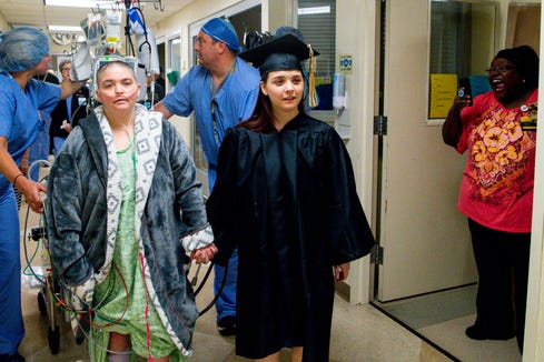 Jaszmon Perez takes her mother, Bridget Perez, on a lap around the hospital floor during a special graduation at Vanderbilt University Medical Center Tuesday, May 21, 2019, in Nashville, Tenn. Bridget Perez, 36, is on ECMO waiting for a lung transplant and wouldn't have been able to attend the graduation.