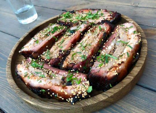 Barbecued pork ribs with smoked black garlic glaze, benne seeds and cilantro.