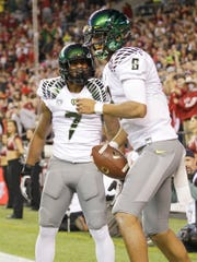 Oregon quarterback Marcus Mariota, right, celebrates his touchdown against Washington State with Keanon Lowe (7) during a game Sept. 29, 2012.