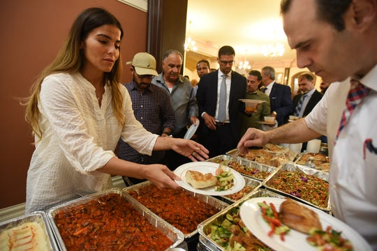 Cagla Celikel (foreground) of Paterson, receives a plate of food during the Mayor Andres Sayegh's Inaugural Iftar at City Hall in Paterson on 05/20/19. Paterson holds its first official Iftar meal, to break the Ramadan fast sponsored by the city in recognition of the city's large Muslim American population.