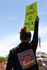 A woman holds up a protest sign during a protest in Englewood on Tuesday May 21, 2019 to stand up and speak out against the numerous bills under consideration and being passed that would overturn Roe v. Wade and a woman's right to control her body.