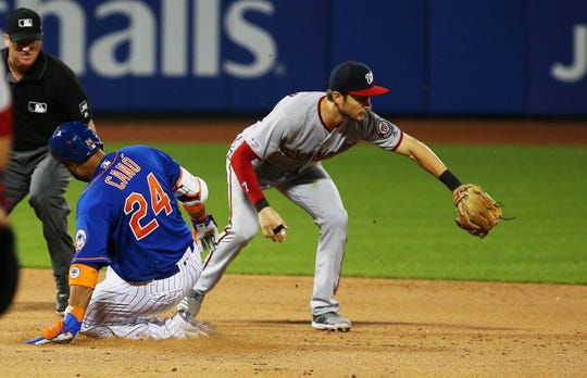New York Mets pinch hitter Robinson Cano (24) slides safely into second base after hitting a double against the Washington Nationals during the sixth inning at Citi Field.