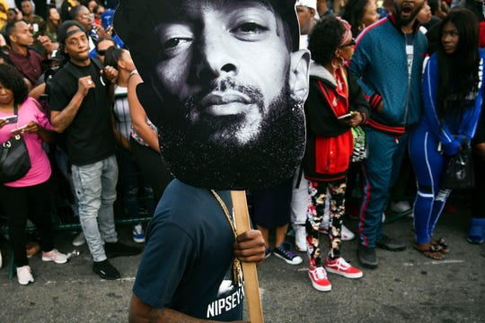 A  man hold sign displaying the image of Nipsey Hussle in front of the Marathon Store during his funeral on April 11.