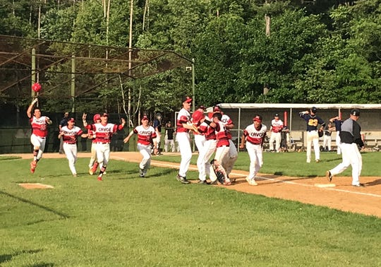 Emerson baseball players celebrate with Joe Carmosino (center, in batting helmet) after the senior hit the winning RBI single to give the Cavos a 1-0 win over Saddle Brook in Monday's state tournament opener.