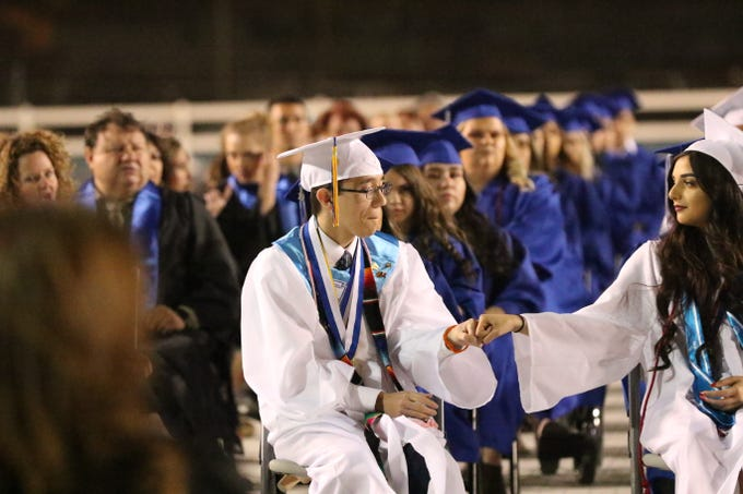 Carlsbad valedictorian Logan Antiporda recieves a fist bump from fellow Carlsbad High School senior and salutatorian Jennah Groves May 20.