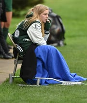 With a pair of crutches by her chair, Novi Wildcat injured goalie Abbey Pheiffer sits on the sidelines and watches her teammates on May 20.