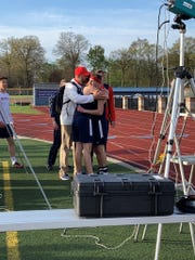 Livonia Franklin's Michael Mackiewicz is hugged by coaches and teammates after completing his final race for the Patriots.