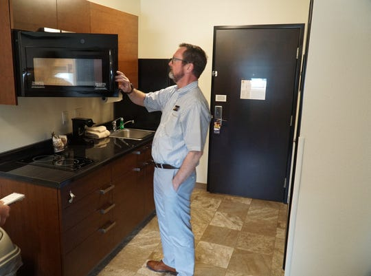 My Place Hotels Wixom general manager Jeff Cobb checks out a room's kitchenette. Guests can heat up food on a small stove or use the room's microwave oven. Each room also has its own fridge with ice dispenser.