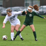 Livonia Stevenson Spartan Sam Kuszynski and her teammates did what they could to keep Novi's Avery Fenchel, right, away from the ball on May 20. But Fenchel still ended up scoring the game's only two goals.