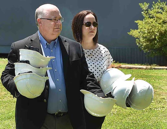 Westminster Christian Academy head of school Scott Davis and Michelle Nezat, director of institutional advancement, collect hard hats that were used at the groundbreaking ceremony.