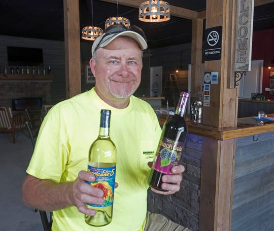 Derek Frazier, the owner of Frazier's Country Wines, shows off two of his most popular wines May 21. The winery is launching a new running club called Bayou Chico Chasers.