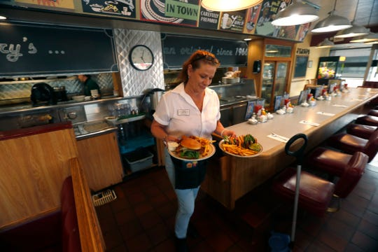 Kimberly Yellick brings food to customers at Jerry's in Phoenix, Ariz. on May 20, 2019.